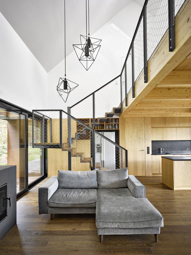 Ústřední společná obývací část je otevřená nejen do stran, ale i nahoru do podkroví. Nejsou tu žádné zdi, vymezují ji prosklené stěny, stropy a vestavěný nábytek, který spolu s dveřmi a obklady z téhož materiálu vytváří jednolitou, čistě funkčně členěnou plochu.