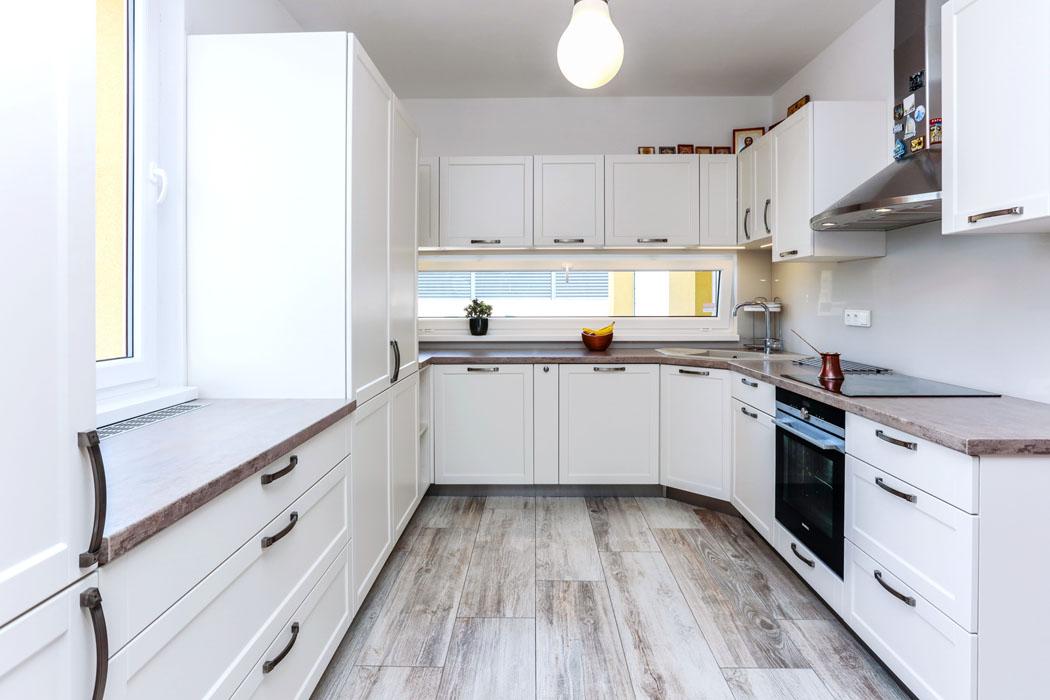 Kuchyň je zařízena praktickou linkou  vetvaru písmene U. Vinylová podlaha  sdezénem starého dřeva krásně zapadá dovýběru jemných barev  apřírodních materiálů, které vytvářejí harmonickou atmosféru.