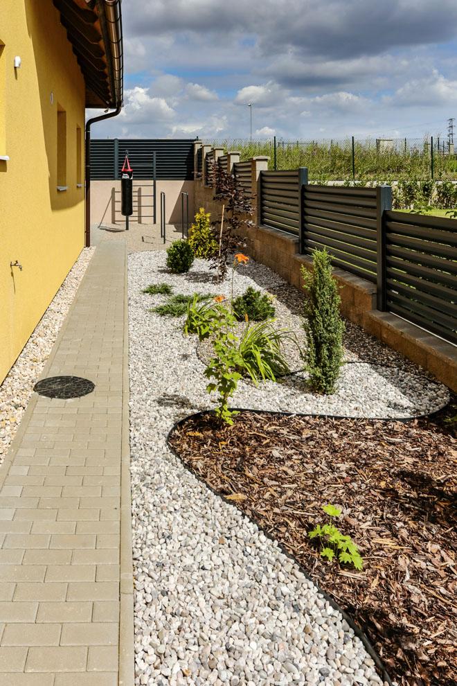 Originálně řešená zahrada kombinuje zeleň smulčovanými záhony, oblázky azpevněnými plochami ze zámkové dlažby. Podzemní závlahový  systém je rozveden kjednotlivým rostlinám, takže ani kapka vody nepřijde nazmar.
