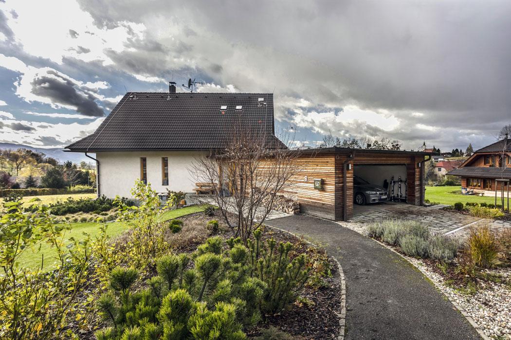 Na příjezdovou cestu navazuje garáž obložená dřevem, která je citlivě zakomponována do hmoty domu.