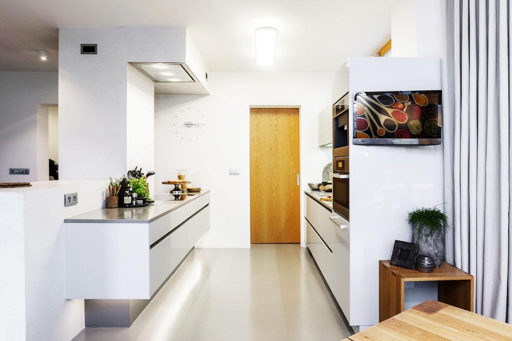 Také kuchyně je zajímavě komponovaná a nezapře důmyslnou geometrickou hru s tvary a prostorem. Z tohoto hlediska jde onebývalou důslednost celého konceptu domu.