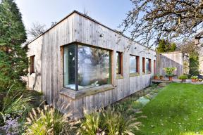 Dřevěná fasáda poletech zestárla dokrásna abarevně ladí sokolní přírodou, která dům obrůstá. Ten dnes vypadá, jako by natom místě stál odjakživa. Pokaždé mě při návštěvě domu znovu nadchne zelená střecha svýhledy naVysoké Mýto.