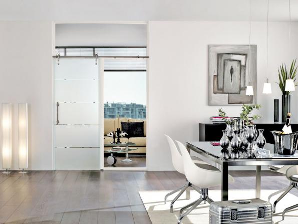 Posuvné celoskleněné dveře nastěnu smotivem skla DUO 151-1 vkombinaci sposuvným nerezovým kováním Art. Dveře jsou vyrobeny zvysoce bezpečnostního skla (PRÜM)