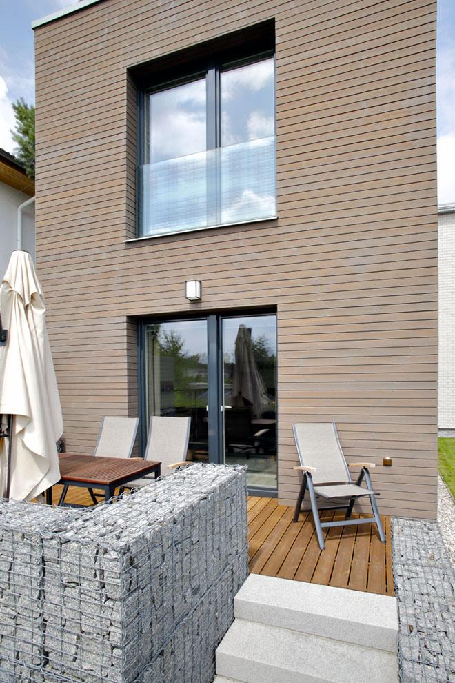 Zahradní trakt, dvoupodlažní hmota splochou střechou, svelkými prosklenými plochami ashorizontálním dřevěným obložením.