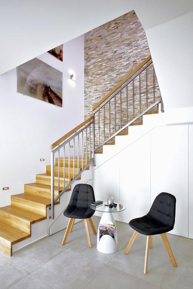 Středobod dispozice tvoří vstupní aschodišťová hala, propojující kuchyňskou část, obývací pokoj imístnosti vpatře. Je zařízena jako obytná  svestavěnými úložnými prostory pod schody.