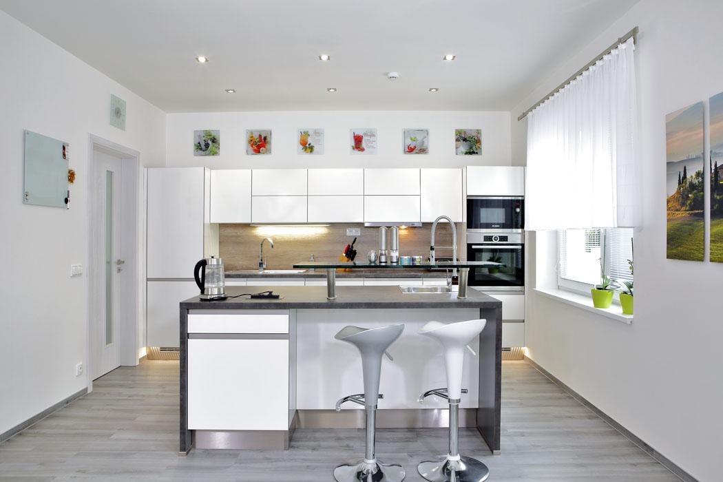 Vybavení interiéru tvoří funkční nábytek, design je založen nakombinaci bílé, šedé asvětlého přírodního dřeva. Kuchyň svarným ostrůvkem, barovým sezením ajídelním stolem je samostatná místnost orientovaná doulice.