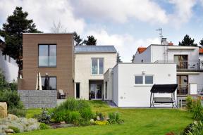 Ze zahrady se dům skládá ze dvou hmot odlišených tvarem střechy aobkladem fasády.Horizontální dřevěný plášť zThermowoodu jemně kontrastuje se světlými cihelnými pásky. Přízemní objekt garáže tvoří mezičlánek abariéru mezi obytnou stavbou asousedním domem.