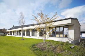 """""""Jednoduchost tvaru střechy vyvažuje účelný prostor – venkovní ivnitřní zároveň – klasická veranda je zároveň molem, které provede člověka odveřejné, převážně pouze zatravněné, přehledné zahrady přes polosoukromou, osázenou ovocnými stromy vpravidelném rastru, až podivočejší svět zadní volně rostoucí louky."""""""