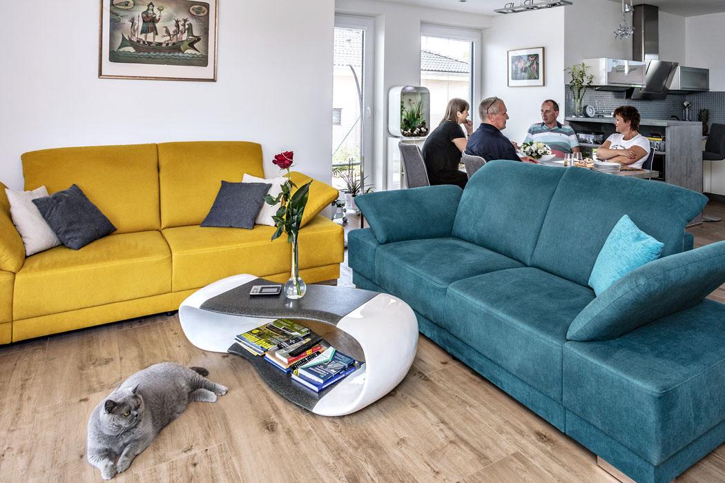 Obývací pokoj nabízí pohodlné sedačky snastavitelnými bočními opěrkami. Ujídelního stolu si smajiteli povídáme ozkušenostech se stavbou iprovozem domu.