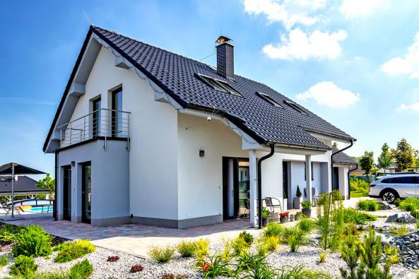 Směrem kpříjezdové komunikaci nabízí dům pohled nazajímavě členěnou fasádu apříjemnou barevnou kombinaci bílé ašedomodré termoizolační omítky ačerné střešní krytiny.
