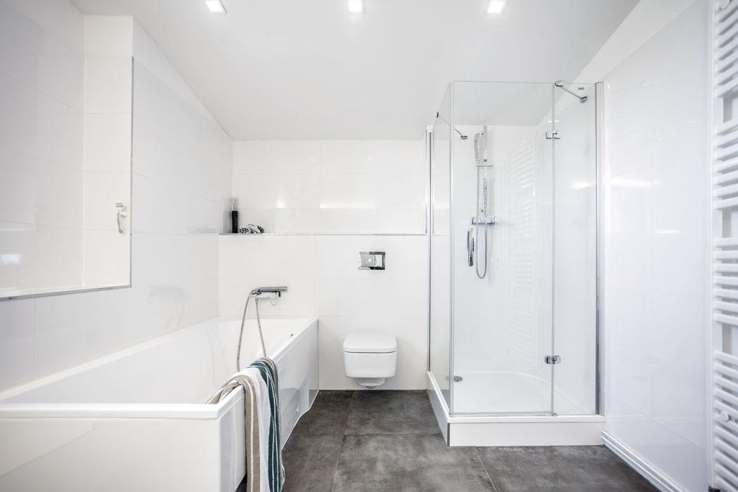 Obklady avybavení koupelny dodalo studio SIKO. Bílá barva asklo prostornou koupelnu opticky ještě více zvětšují aprosvětlují.