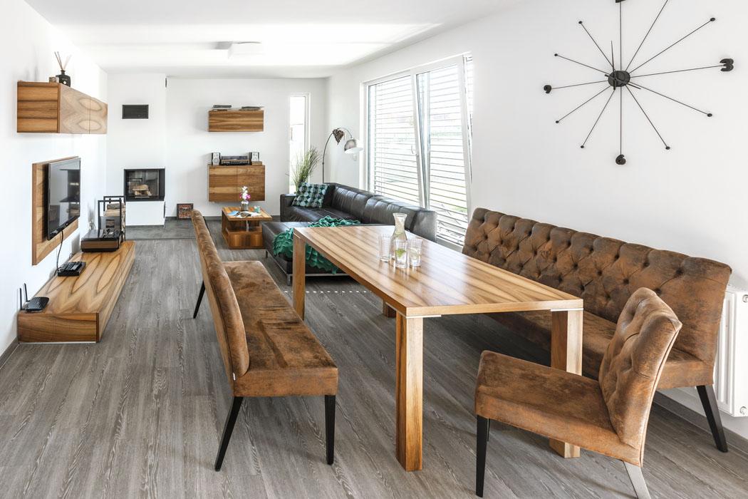 Nazakázku vyrobený nábytek skrásnou ořechovou dýhou dodal interiéru výrazného ducha. Harmonicky je doplňuje sezení skoženým potahem vestylu vintage.