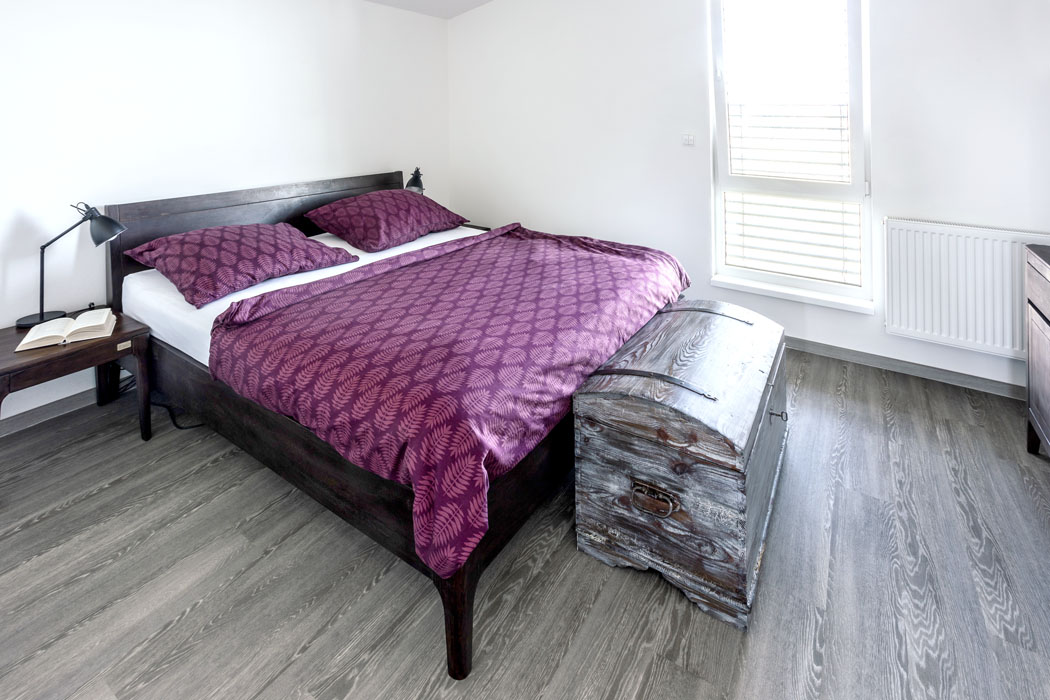 """Také ložnice je vybavena stylovým dřevěným nábytkem. Truhla navozuje atmosféru """"solidních"""" starých časů apřipomíná, že nábytek byl dříve především bytelný apraktický. Což jsou hodnoty, které vyznávají iobyvatelé tohoto domu."""