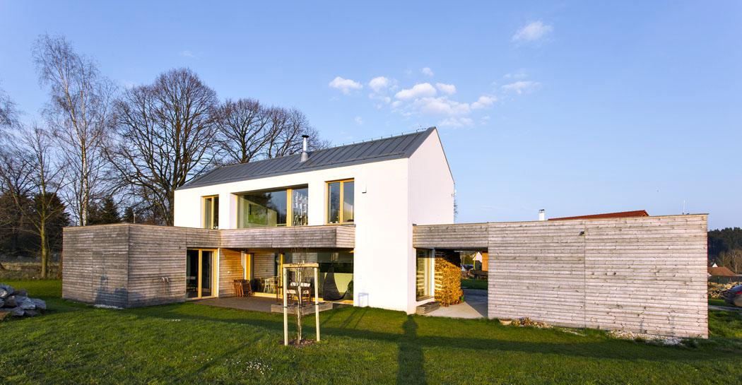 Pohled naseverozápadní fasádu. Velkorysá okna zajišťují přímou vazbu mezi interiérem aokolní zahradou. Koncept domu je založen naprůniku dvou různorodých forem. Tradiční patrový dům zakončený sedlovou střechou doplňuje dřevem obložená forma vpřízemí.