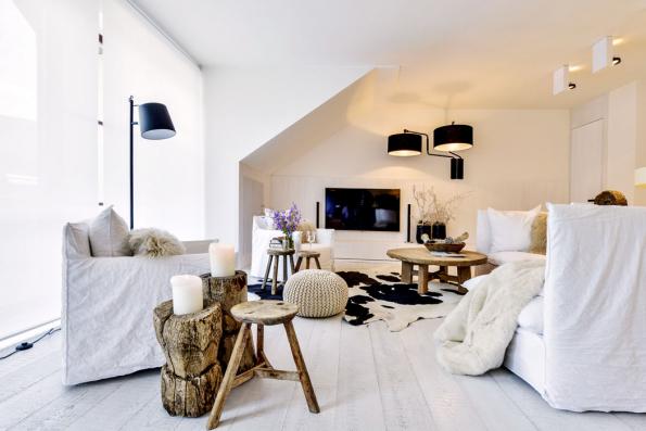 Ručně vyráběný nábytek ze dřeva spřirozenou patinou opotřebení působivě vyniká napozadí bělené podlahy apřírodního lnu potahů. Okontrast se vneutrálně laděném interiéru postaral koberec zhověziny amoderní černé lampy.