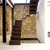 Kovové lomenici schodiště vytváří zdivo zlomového kamene až divadelně působivé pozadí… Přísná pravoúhlost apravidelný rytmus prvního dokonale ladí sživelnou nepravidelností druhého.