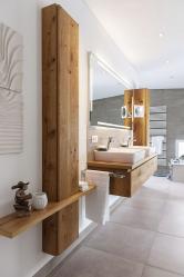Vjednoduchosti je krása – hmotově čistý nábytek zmasivního dřeva doplňuje šedá dlažba, bílé ručníky aplastika vpopředí. Výsledek je půvabný asvěží, stejně jako celá koupelna.