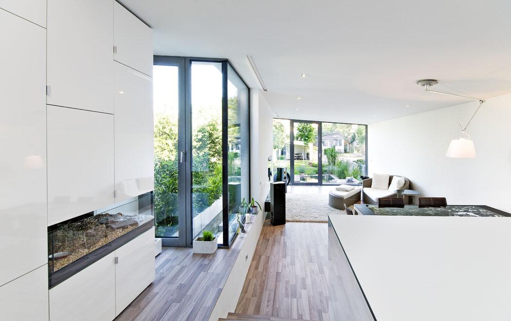 Přistavěná společná obývací část svelkým prosklením působí dojmem, jako by byla součástí zahrady. Převažuje tu ladění dočerné abílé barvy, zvýrazněné dřevěnou třívrstvou podlahou.