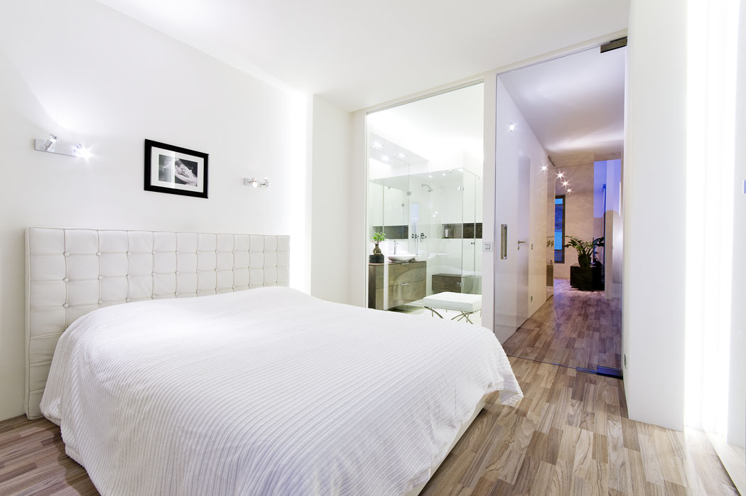 Ložnici vprvním patře odděluje odschodiště aodkoupelny jen čiré sklo. Denní světlo se tak dostává dohloubky dispozice, dům působí prostorněji avzdušněji.