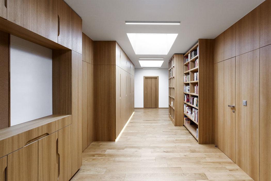 """""""Obytná"""" chodba vedruhém podlaží je vybavena nábytkovou sestavou přesně podle přání majitelů. Kromě vestavěných skříní tu jsou iposuvné knihovny adalší úložné prostory, nedílnou součástí jsou ibezzárubňové dveře integrované vdřevěném obložení stěn. Díky velkým střešním oknům, určeným speciálně pro ploché střechy, tu panuje příjemná vzdušná atmosféra."""