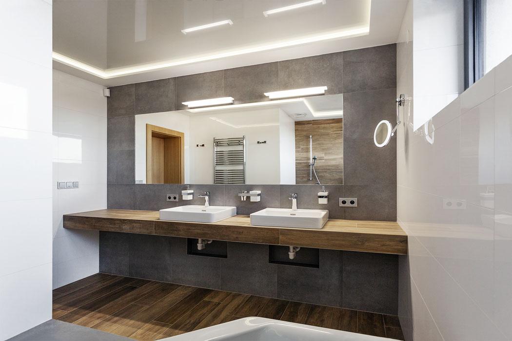Koupelně vedruhém podlaží udává tón velkoformátový obklad sdekorem pohledového betonu adlažba imitující dřevěná prkna. Stejná byla použita inaumyvadlovou desku.