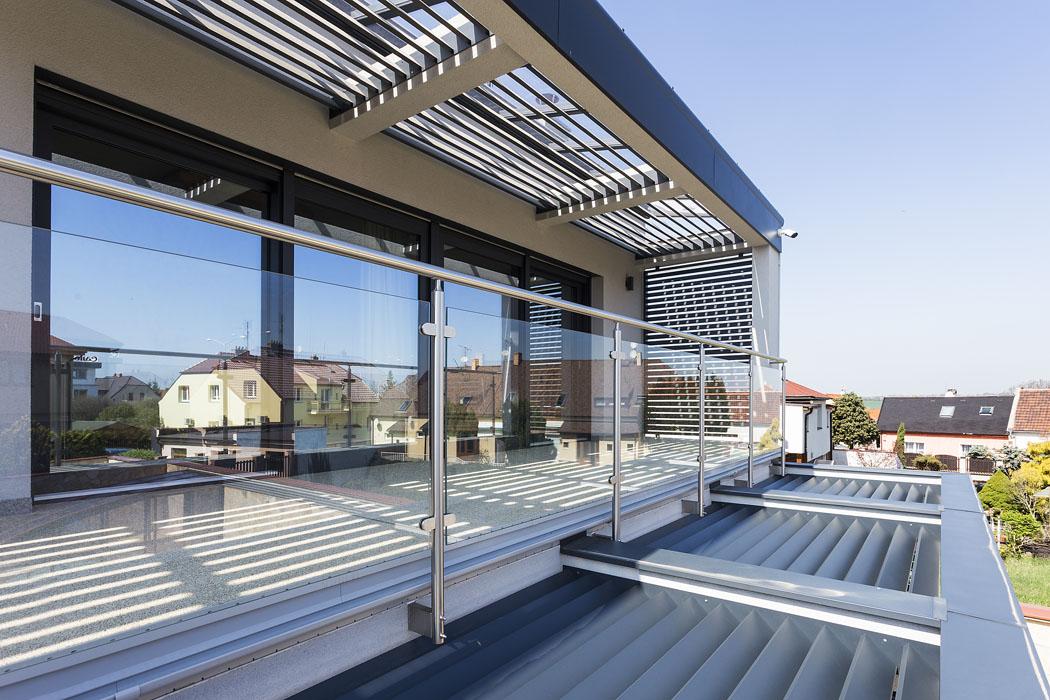 Terasy vobou podlažích jsou účinně zastíněny slunolamy shliníkovými lamelami. Nad druhým podlažím je navíc istříška zčirého skla naochranu před deštěm.