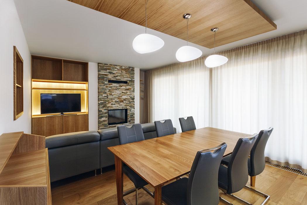 Obývací pokoj vedruhém podlaží. Téměř veškeré vybavení interiéru vdomě bylo vyrobeno nazakázku podle návrhu Anety Stružkové. Převažuje přírodní dubová dýha, olejová povrchová úprava jí dodává nádherný zlatavě hnědý odstín.