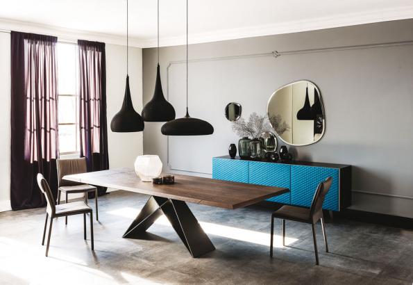Černě lakovaná ocelová podnož vespojení sdeskou zořechového dřeva vnese dointeriéru dynamiku aeleganci. Stůl Premier Wood Design nabízí společnost Cattelan Italia.