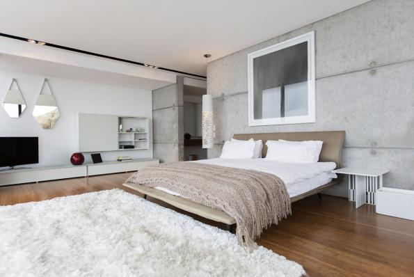 Neutrální barevnost betonových panelů abílé omítky prohřívá dřevěná podlaha abytový textil. Čalouněné čelo postele, hrubě pletený přehoz ahuňatý koberec svysokým vlasem příjemně oživují industriální, téměř nebarevný interiér svou strukturou.