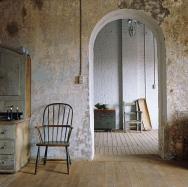 Proměnlivá barevnost několika vrstev výmalby dokonale ladí spřírodní barvou starých prken napodlaze iotlučeným nábytkem. Bílý nátěr cihlové stěny vpozadí nechal vyniknout její strukturu. Právě harmonická kombinace barev aodlišných struktur dokáže zútulnit velkoryse prázdný interiér vindustriálním stylu.