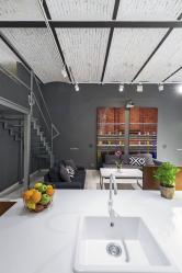 Kontrastní kompozici černých ocelových nosníků sbíle natřenými klenbami citlivě doplňuje antracitová výmalba. Interiér prohřívají azútulňují pestré olejomalby, dřevěný nábytek, zeleň aovoce.