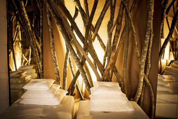 Příroda prochází celou relaxační zónou Romantik hotelu Turm včetně odpočívárny. Dekorativní azároveň rafinovaný prostorový předěl byl vytvořen zkmenů stromů.