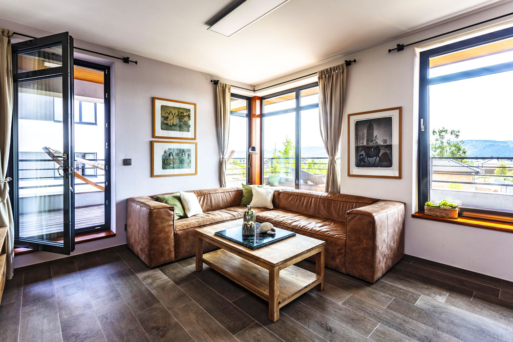 Odpočinková sekce v rohu hlavní obytné místnosti je vybavena koženou sedací soupravou. Okny je dobře vidět prostorná terasa, v pozadí zalesněné panoráma.