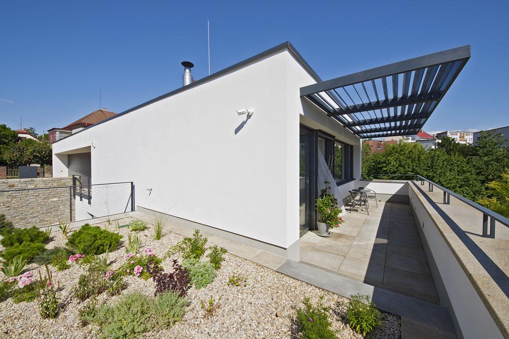 Při pohledu zulice zůstávají většina domu, terasy izahrada skryty pod svahem. Byt vnejvyšším podlaží funguje nezávisle, jižní prosklená fasáda je stíněna pevným slunolamem socelovou konstrukcí.