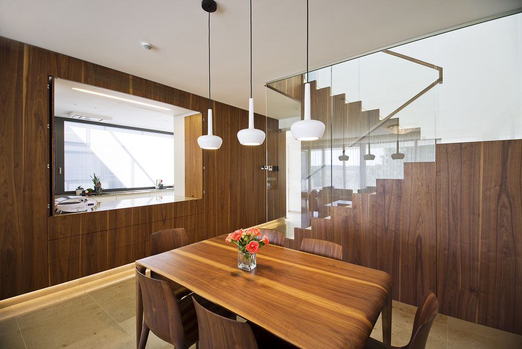 """Kuchyň je vložena dospolečné obývací části domu jako monoblok obložený ořechovým dřevem. Vložené """"okno"""" ji umožňuje podle potřeby uzavřít, nebo propojit sjídelnou aobývacím pokojem. Pracovní plochu osvětluje okno doatria, praktické zadní dveře vedou doobslužné zóny se spíží akomorou. Žulové pracovní desky se dobře udržují, dlouho vydrží akrásně ladí smramorovou podlahou."""