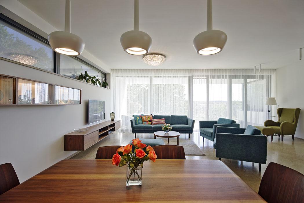 Doobývacího pokoje přichází slunce především čelní prosklenou stěnou, která poskytuje výhled dozeleně. Dalšími zdroji světla jsou pásové okno vseverní fasádě, prosklené atrium aotevřený schodišťový prostor.