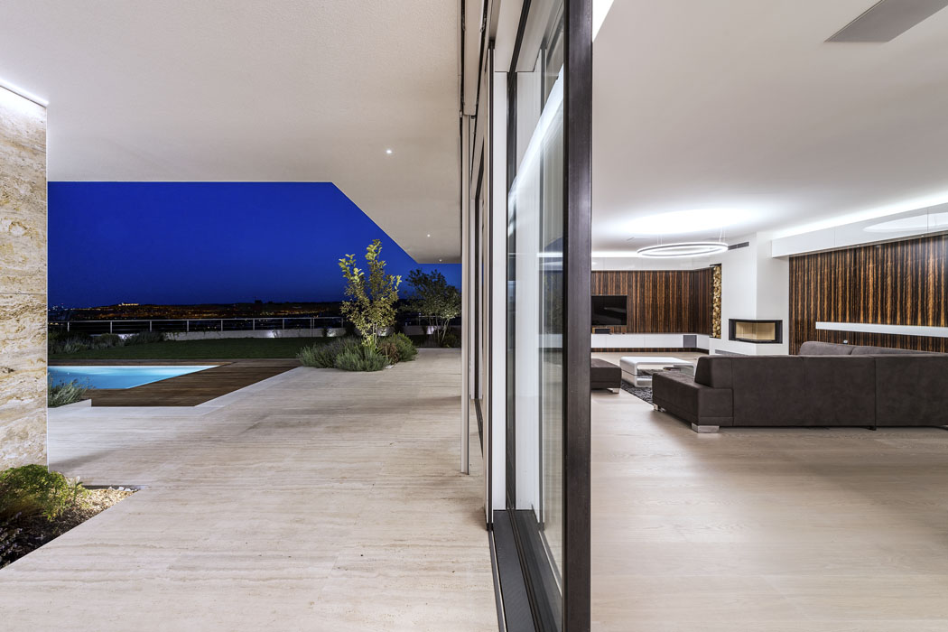 Podlaha obývacího pokoje bezbariérově přechází vevenkovní dlažbu. Jemná barevnost akresba běleného dubového dřeva harmonicky splývá sbarevností ikresbou travertinových desek nakryté terase.