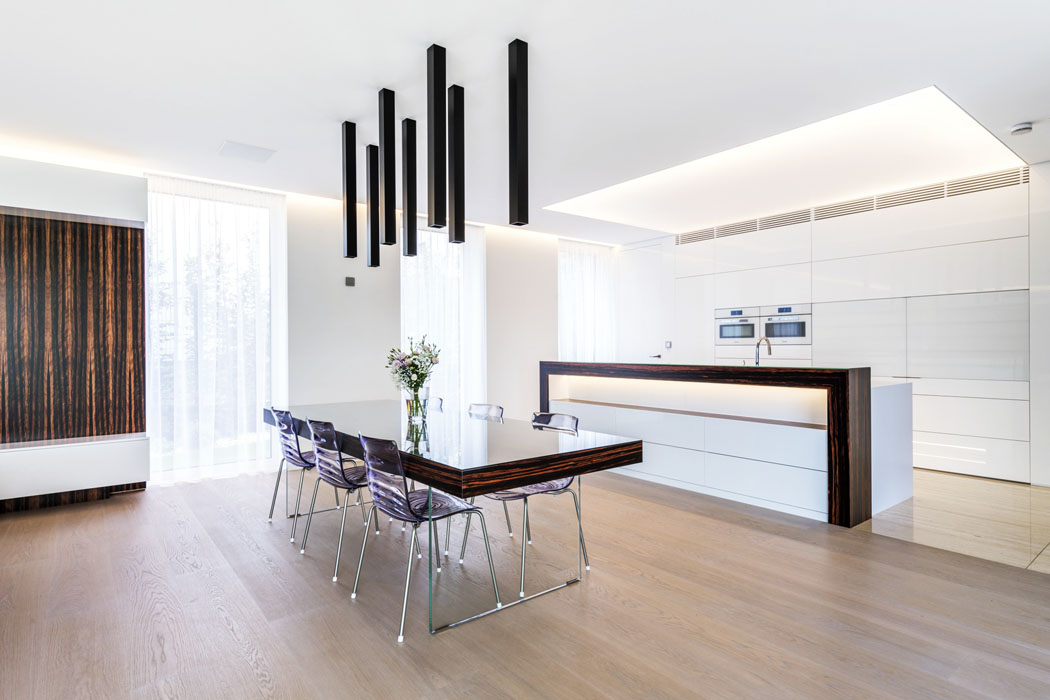 Bíle lakovaná kuchyňská linka se skládá zkompaktní sestavy ustěny (sintegrovanými dveřmi dotechnické místnosti) aostrovního varného centra. Má příjemné rozptýlené osvětlení – LED zdroje jsou zapuštěny vestropním podhledu zaprůsvitnou fólií Barisol.