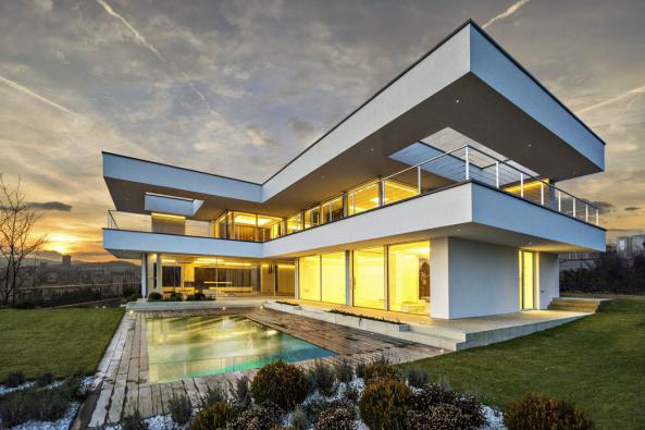 Čistý geometrický tvar, výrazné přesahy stropních desek, horizontální prosklené plochy, subtilní ocelové zábradlí, dům hovoří charakteristickým jazykem funkcionalistické architektury. Sním konvenují itravertinová dlažba kolem domu, venkovní schodiště aobrubníky zbílého betonu. Minimalisticky je řešen ibazén – vodní plochu zakrývá roleta  zapuštěná vdřevěné palubě.