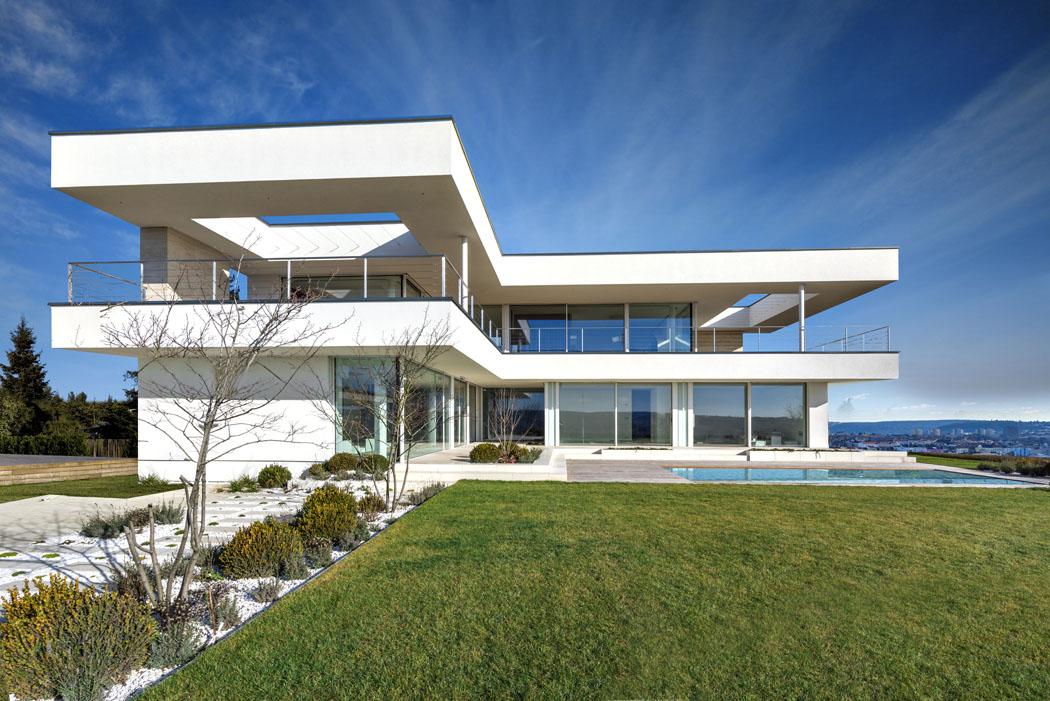 Dispozice horního podlaží je oněco menší než přízemí. Tvar stavby navenek dotvářejí  výrazné železobetonové moniéry, které zároveň zajišťují žádoucí zastínění teras.
