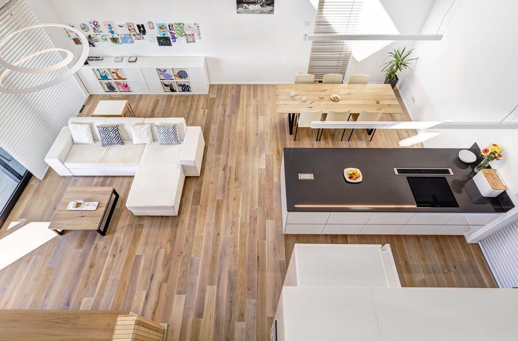 Nad obývacím pokojem je umístěna otevřená galerie, lemovaná zábradlím zčirého bezpečnostního skla, aby nic nenarušilo otevřený avolný prostor. Dobělostného interiéru si majitelé nechali udělat podlahu ačást nábytku zběleného dubového dřeva.