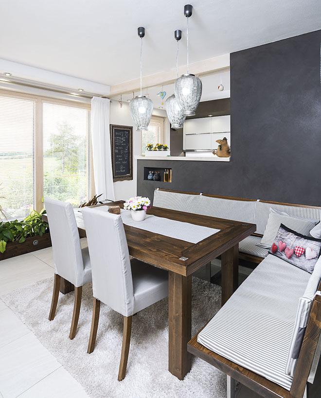 Kuchyň je přes polovysokou příčku částečně otevřena do společného obývacího prostoru. Přírodní materiály a tlumené barvy dodávají interiéru příjemný harmonický a uklidňující výraz.