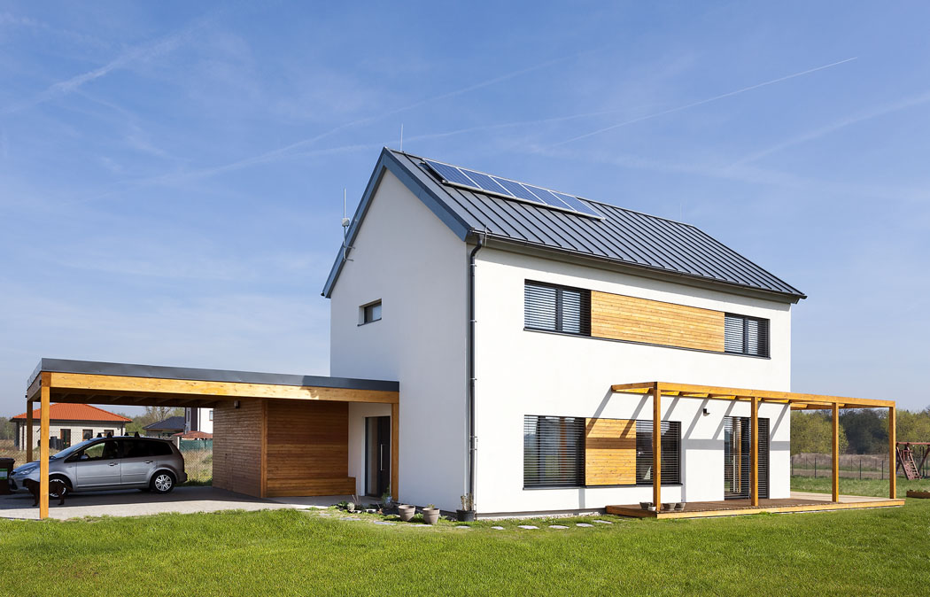Nadřevostavbu jednoduchého tvaru se sedlovou střechou navazuje zvýchodu ajihu terasa spergolou aze západu kryté stání pro dvě auta anevytápěný sklad.