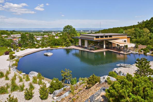 Vbujaré zeleni nakonci malebné obce nedaleko Olomouce stojí nakopci zcela výjimečný rodinný dům, který realizovala firma specializující se nastavbu jezírek. Ojedinělá prosklená stavba citlivě zapadá dokrajiny anabízí nádherné výhledy dookolí. Její specifický výraz umocňuje velké jezero skameny, vodopády ahorskou flórou.