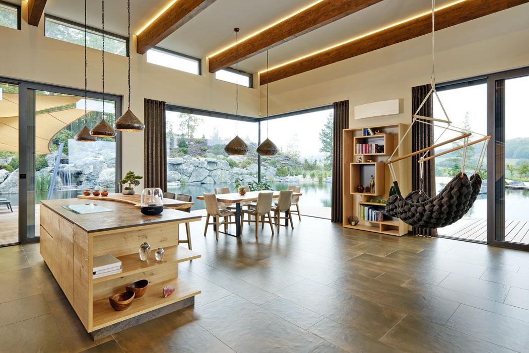 Dům je jasnou ukázkou toho, že přírodní materiály jsou nesmrtelné, dodávají každému interiéru přirozený charakter. Všechny obývací místnosti jsou navíc mistrně propojeny přes velké prosklené plochy svenkovní terasou ajezerem.