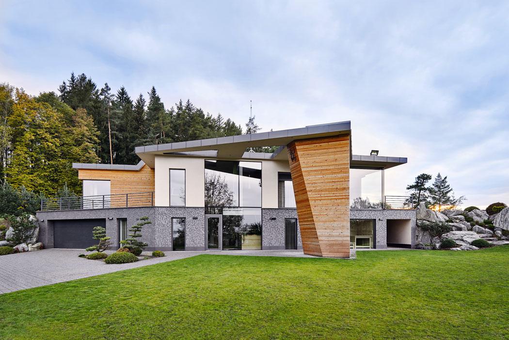 Hlavní vstupní fasáda – průčelí domu – asi nejlépe vystihuje hmotu acelkový výraz stavby sdominantou masivního pilíře.