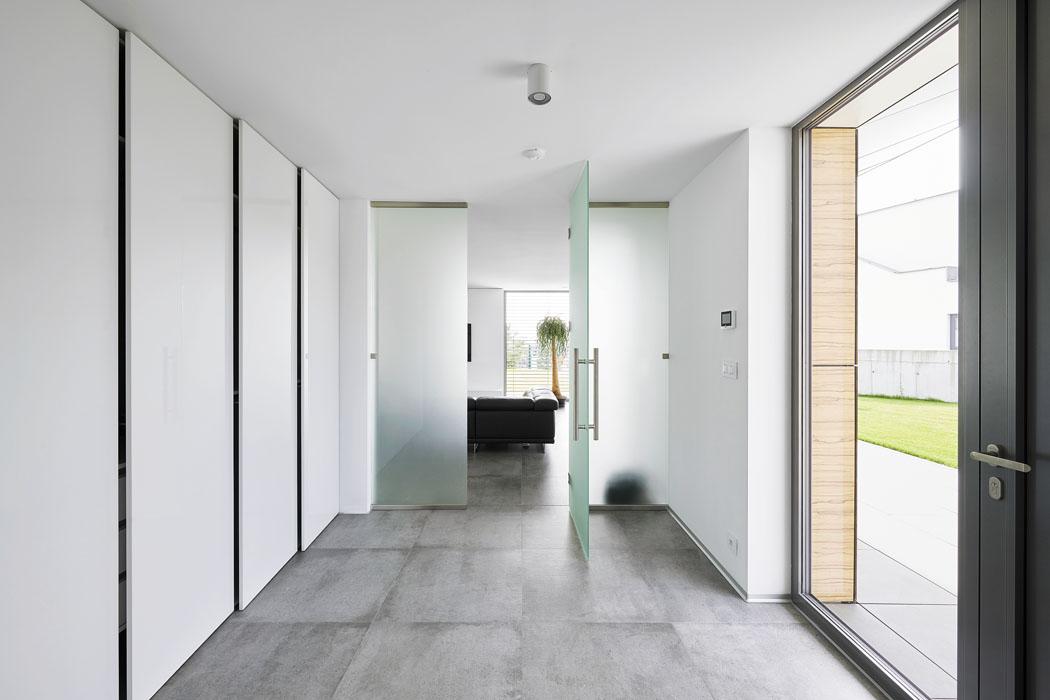Vstupní halu odděluje odobývacího prostoru stěna zmléčného skla. Vcelém domě jsou důmyslně zabudovány úložné prostory, jejichž přítomnost neprozrazují žádné úchytky ani jiné zbytečné detaily.