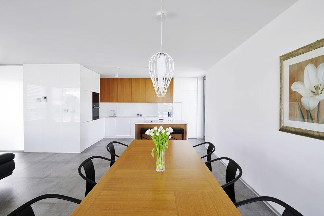 Minimalistickou kuchyňskou linku architekti navrhli zlakovaných MDF desek svysokým leskem vkombinaci steakovým dřevem, zněhož je vyroben ijídelní stůl.