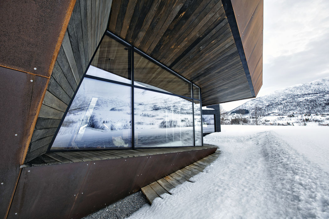 Fasádu domu tvoří velkoformátové, úzkými profily lemované prosklené plochy vkombinaci scortenovými plechy asmrkovým obložením.