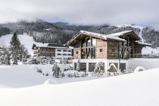 Architektura hotelu iokolních challetů reaguje natradiční alpské stavby, stavební prvky  amateriály, zároveň je však moderní amaximálně technologicky vyspělá.